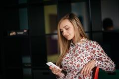 Kawiarnia z wifi Młoda atrakcyjna długie włosy kobieta używa mądrze telefon przy restauracją podczas gdy siedzący Zdjęcie Royalty Free
