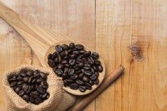Kawowa fasola na łyżce i cynamonie nad drewnianym ta workowej i drewnianej Obraz Royalty Free