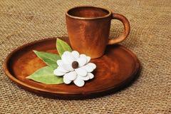 Kawowa gliniana filiżanka i oryginalny domowej roboty kwiat od dyniowych ziaren i zatoki opuszczamy na round ceramicznej tacy na  zdjęcie royalty free