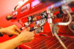 Kawowa maszyna robi dwa kawie na czerwonym tle Zdjęcia Stock