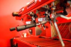 Kawowa maszyna robi dwa kawie na czerwonym tle obraz stock