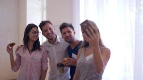 Kawowa przerwa, szczęśliwa grupa młodzi pracownicy zabawę i robi fotografiom z telefon kamerą wpólnie zbiory