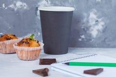 Kawowa przerwa z czekoladowymi muffins, notatnikiem i ołówkiem, Zdjęcia Royalty Free