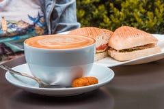 Kawowa sztuka i panini przy plenerową kawiarnią Fotografia Stock