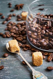 Kawowe fasole i brown cukier na rocznika tle Zdjęcia Stock