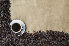 Kawowe fasole i filiżanka kawy z burlap zdjęcia royalty free