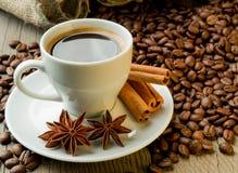 Kawowe fasole i filiżanka z cynamonem i anyżem zdjęcia royalty free
