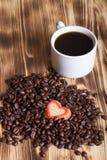 Kawowe fasole i kawa w białej filiżance na drewnianym stole dla backgro Zdjęcie Stock
