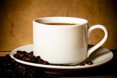 Kawowe fasole i kawa w białej filiżance na drewnianym stole naprzeciw a Zdjęcia Royalty Free