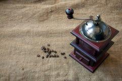 Kawowe fasole i kawowy ostrzarz, zamykają up na tle Obraz Royalty Free