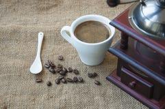 Kawowe fasole i kawowy ostrzarz, zamykają up na tle burlap worek Zdjęcia Royalty Free