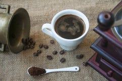 Kawowe fasole i kawowy ostrzarz, zamykają up na tle burlap worek Fotografia Stock