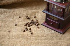 Kawowe fasole i kawowy ostrzarz, zamykają up na tle burlap worek Fotografia Royalty Free