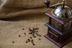 Kawowe fasole i kawowy ostrzarz, zamykają up na tle burlap worek Obraz Royalty Free