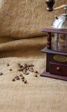 Kawowe fasole i kawowy ostrzarz, zamykają up na tle burlap worek Obrazy Royalty Free