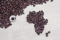 Kawowe fasole i zabawkarska filiżanka z kawą, pojęcie Zdjęcie Royalty Free