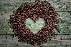 Kawowe fasole jako serce na starym wieśniaka stole Odgórny widok Obrazy Royalty Free
