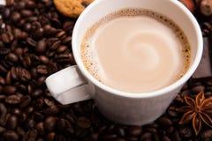 Kawowe fasole kawowe z śmietanką w filiżance Obrazy Royalty Free