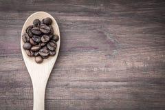 Kawowe fasole na łyżkowym i drewnianym tle obrazy stock
