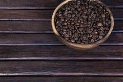 Kawowe fasole na ciemnym drewnianym tła grunge, kawa w drewnianym talerzu na drewnianym Zdjęcie Royalty Free