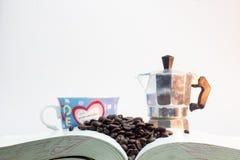 Kawowe fasole na gęstej książce z szkłem kawa, Szklana kawa Zdjęcie Stock