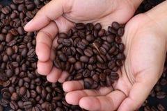 Kawowe fasole na rękach obraz royalty free