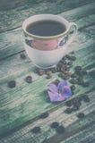 Kawowe fasole, purpury kwitną i filiżanki kawa na starym wieśniak zieleni tle Rocznik Obraz Royalty Free
