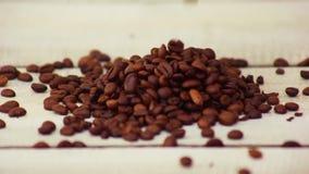 Kawowe fasole spada na drewnianym stole w zwolnionym tempie zbiory wideo