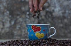 Kawowe fasole spada w białej filiżance Fotografia Stock