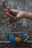 Kawowe fasole spada w białej filiżance Obrazy Royalty Free