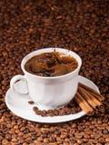 Kawowe fasole spada w filiżankę kawy Obrazy Stock