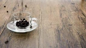 Kawowe fasole spadają na filiżance i na drewnianym tle zbiory