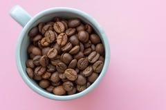 Kawowe fasole w błękitnej filiżance na różowym tle śniadaniowy kawowy pojęcia filiżanki jajko smażący Kawa sia zbliżenie Cukierni fotografia stock