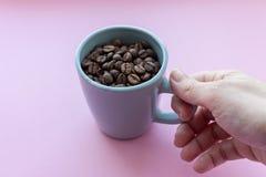 Kawowe fasole w błękitnej filiżance z mienie ręką na różowym tle Śniadaniowy pojęcie z kopii przestrzenią Cukierniany pojęcie zdjęcia stock