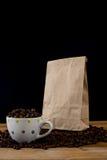 Kawowe fasole w białej filiżance i brown papierowej torbie zdjęcie stock