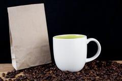 Kawowe fasole w białej filiżance i brown papierowej torbie obrazy royalty free