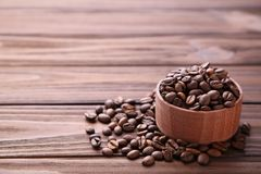 Kawowe fasole w drewnianym pucharze na brązu tle obrazy stock