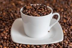 Kawowe fasole w filiżance i wokoło obrazy stock