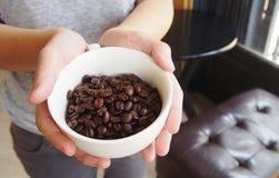 Kawowe fasole w filiżance na rękach Zdjęcia Stock