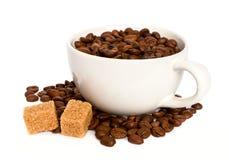 Kawowe fasole w filiżance z brown cukierem obraz stock
