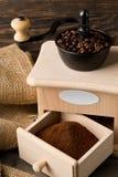 Kawowe fasole w kawowej fasoli ostrzarzu z zmielonym kawa proszkiem Obraz Stock