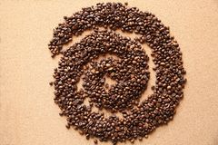 Kawowe fasole w kształcie spirala na drewnianym tle obrazy stock