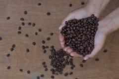 Kawowe fasole w rękach na drewnianym tle Zdjęcia Royalty Free