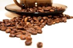 Kawowe fasole wokoło filiżanki z spodeczkiem na biel Zdjęcie Stock