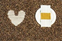 Kawowej fasoli tło z sercem i wiele cygara na bielu talerzu Zdjęcia Royalty Free