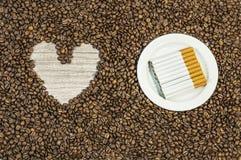 Kawowej fasoli tło z sercem i wiele cygara na bielu talerzu Zdjęcia Stock