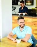 Kawowi pijący żyją długiego Mężczyzna brodaty facet pije cappuccino drewnianej stołowej kawiarni Cukiernianego gościa szczęśliwa  fotografia royalty free