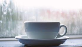 Kawowy czas na deszczowym dniu Moczy szklanego okno i fili?ank? gor?ca kawa Jesieni chmurny pogodowy lepiej z kofeina napojem zdjęcie stock