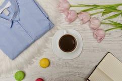 Kawowy kubek, błękitna koszula, różowi tulipany, macaron tort i notatnik z pustymi stronami na stole, Pracujący pojęcie Zdjęcia Royalty Free