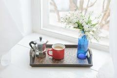 Kawowy kubek, metalu kawowy producent, kwitnie na drewnianej tacy na parapecie Zdjęcia Stock